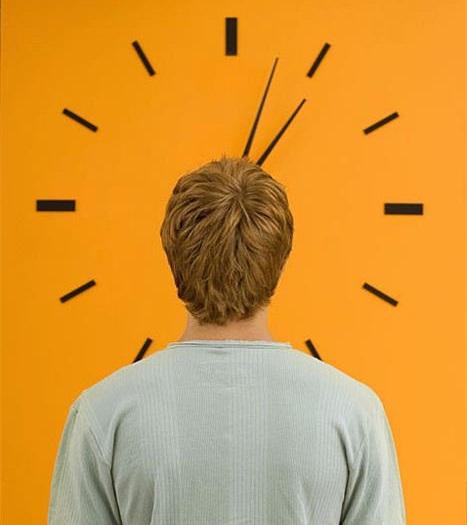 Young man staring at large orange wall clock, rear view